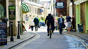 image of a street with a man riding a bike center of camera
