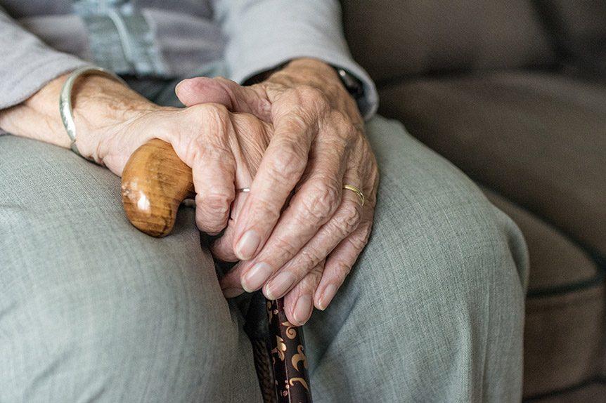 elderly persons hands holding walking stick